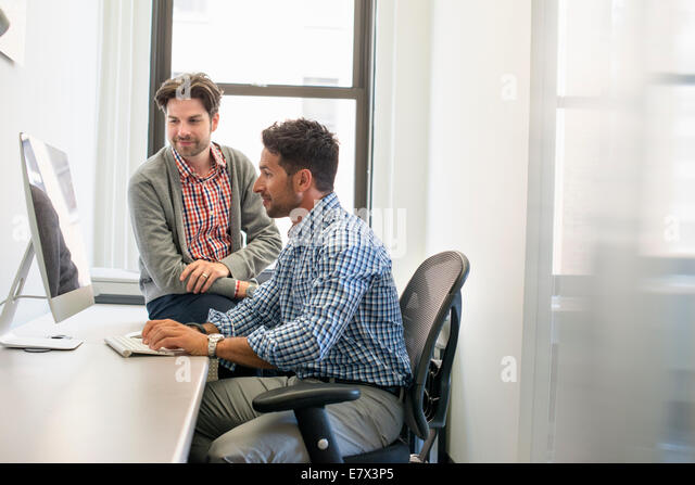 Two business colleagues in an office talking and referring to a computer screen. - Stock Image