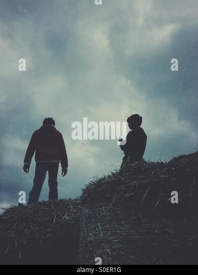 Two boys standing on a haystack - Stock Image