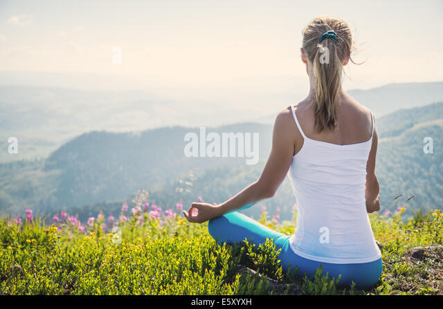 Young woman meditate on the top of mountain - Stock-Bilder