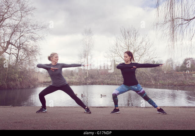 Front view of women by pond face to face lunging - Stock Image