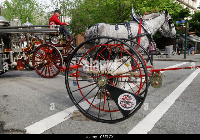 Selection of antique fire fighting equipment being displayed on a street. - Stock Image