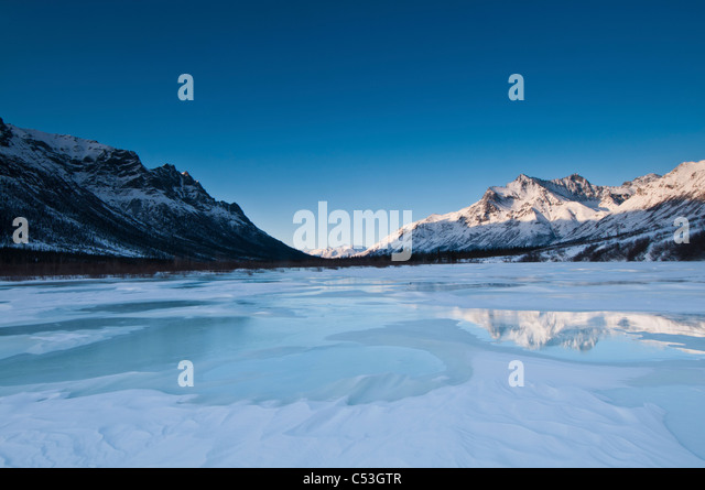 Alpenglow on Boreal Mountain reflects on overflow ice, in Gates of the Arctic National Park, Alaska - Stock Image