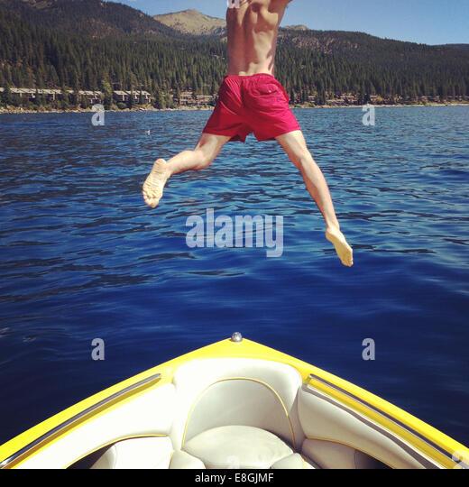 Man jumping off boat into a lake, Lake Tahoe, California, America, USA - Stock Image