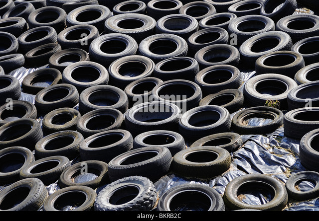 old tyres used on a farm to help protect the winter animal feed from the weather, lancashire, uk - Stock Image