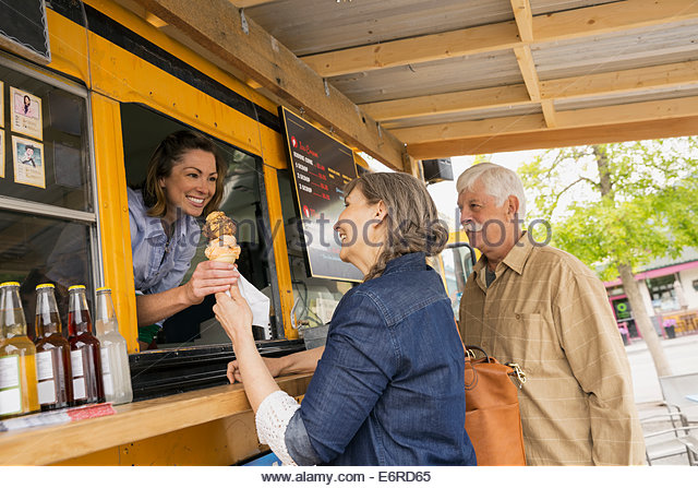Older couple buying ice cream at food truck - Stock Image