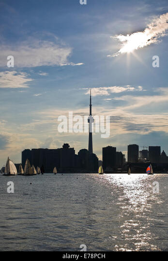 Silhouette of downtown Toronto from the Ontario lake against the sun with high contrast and sailing yachts - Stock Image