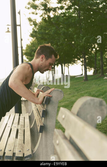 Young man doing press ups on riverside park bench - Stock Image