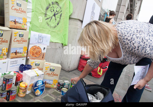 London, UK. 20th July, 2013. More food is added to a 'food bank' as UK Uncut hold demonstrations outside - Stock Image