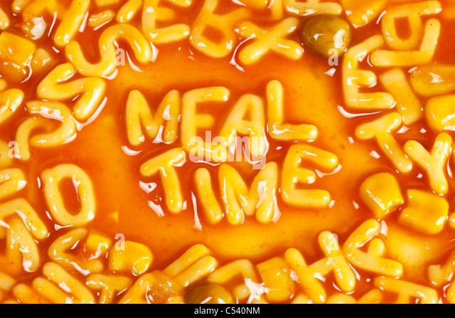 Alphabet shaped pasta forming the word MEALTIME in tomato sauce - Stock Image