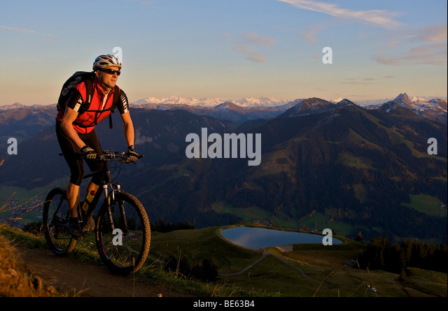Mountainbiker at Hohe Salve mountain in the evening light, Tyrol, Austria, Europe - Stock Image