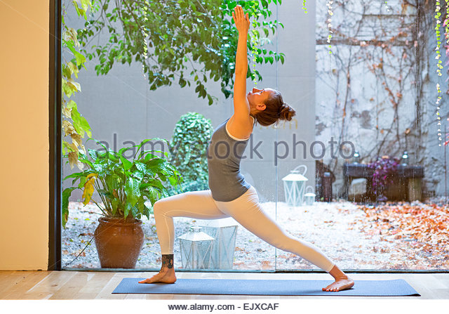 Woman Practicing Yoga, Warrior 1 pose - Stock Image