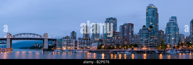 The skyline of downtown Vancouver BC Canada on False Creek as seen from Granville Island at dusk. - Stock Image