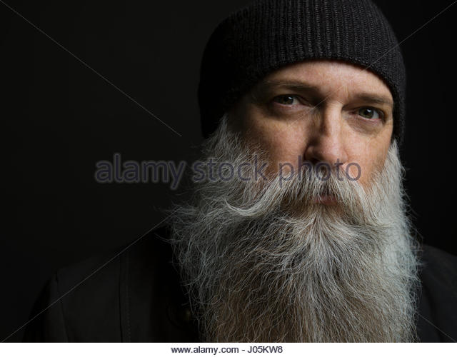 Portrait serious hipster man with gray beard against black background - Stock Image
