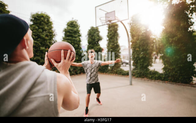 Young man taking shot with friend blocking on basketball court. Streetball players on court playing basketball. - Stock Image