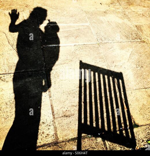 Silhouette of a mum and her baby in a sling next to a deck chair - Stock-Bilder