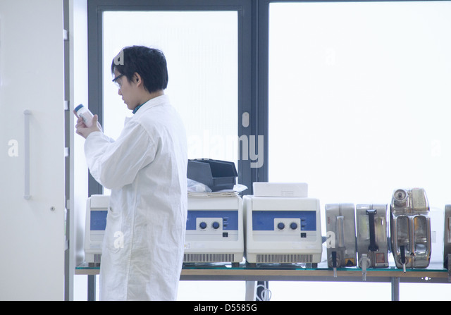 Scientist reading jar label in lab - Stock Image