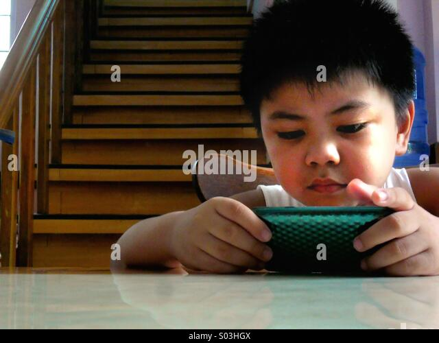 Asian child boy watching or playing on a tablet phone - Stock Image