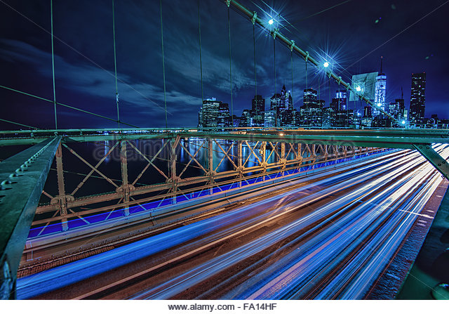 The iconic Brooklyn Bridge with heavy traffic light trails overlooking the Manhattan Skyline and its skyscrapers - Stock Image
