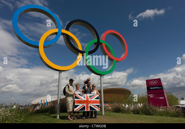 British spectators pose for family photos beneath giant Olympic rings located on a hill in the Olympic Park during - Stock Image