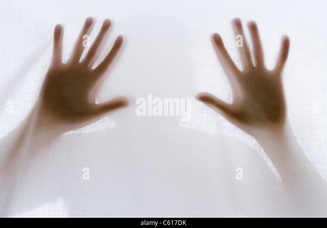 Silhouette of man behind sheet. - Stock Image