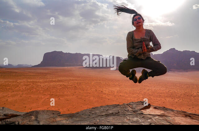 Portrait Of Woman Jumping At Wadi Rum Against Sky - Stock Image