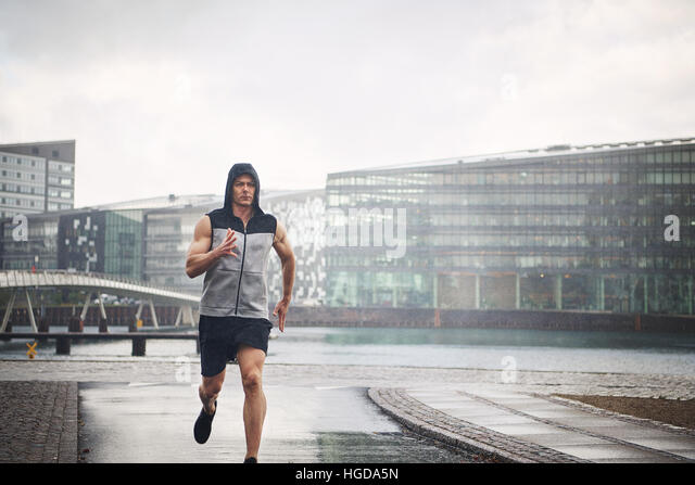 Young athletic man in sportswear running in rain down street. - Stock Image