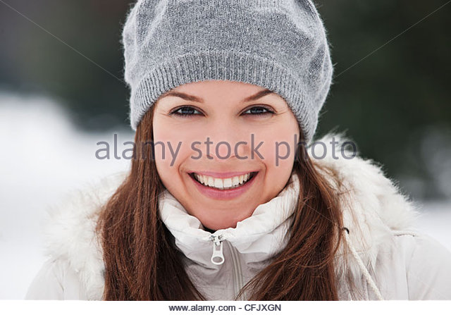 A young woman wearing a grey woolen beret, smiling - Stock Image