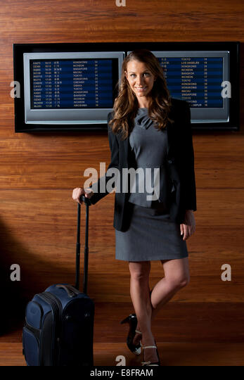 Portrait of a smiling businessWoman at airport in front of destination screens - Stock-Bilder