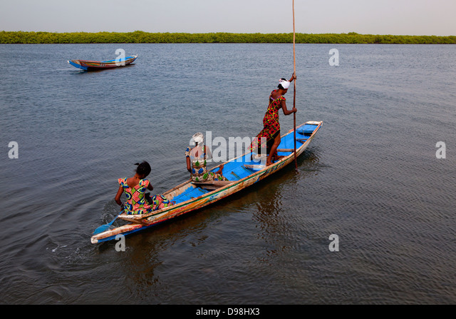 People from the village of Falia rowing traditional pirogue through the bolongs and the mangroves, Palmarin, Senegal, - Stock Image