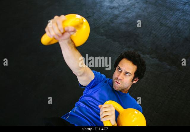 Man on back lifting kettlebells - Stock Image