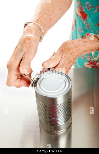 Senior woman's hands with arthritis, struggling to open a can.  - Stock Image