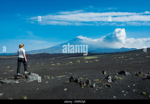 Woman watching Tolbachik volcano, Kamchatka, Russia, Eurasia - Stock Image