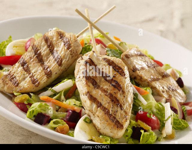 Grilled chicken salad with lettuce, egg, carrot, tomato and onion with dressing - Stock Image