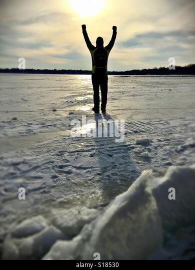 A man standing with arms raised on an icy frozen lake. - Stock-Bilder