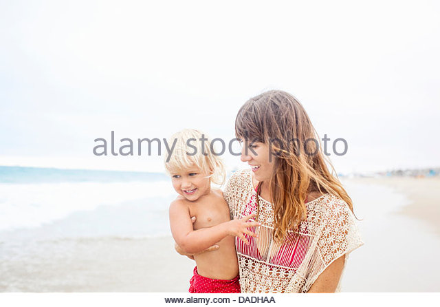 Mother encouraging child to go into the sea - Stock-Bilder