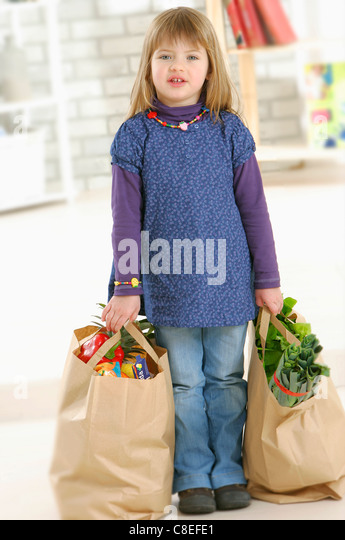 Young girl carrying bags of shopping - Stock Image