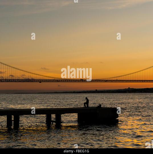 Silhouette Man On Pier Over Tagus River Against Sky During Sunset - Stock-Bilder