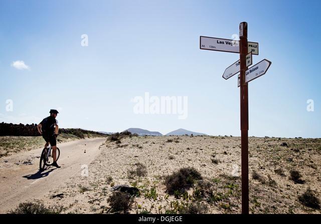 Man mountain biking past sign post, Lanzarote - Stock-Bilder