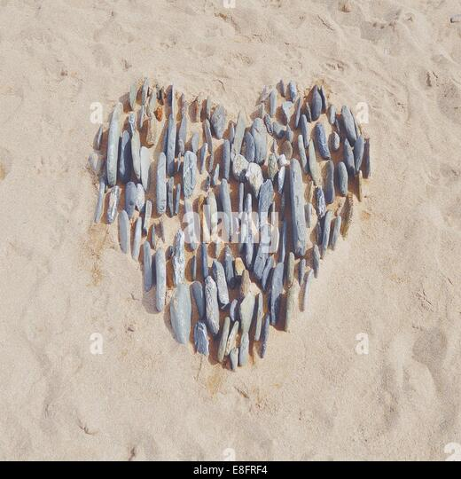 Heart in the sand made with pebbles - Stock-Bilder
