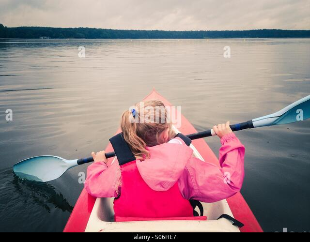 Little girl in kayak on a lake - Stock Image