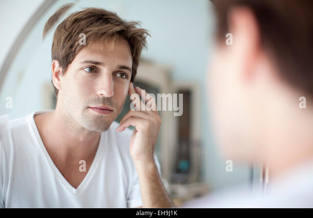 Man looking at self in mirror with concern about his complexion - Stock-Bilder