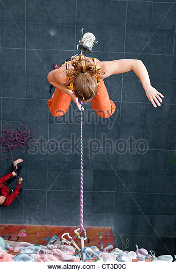 Climber suspended from indoor rock wall - Stock Image