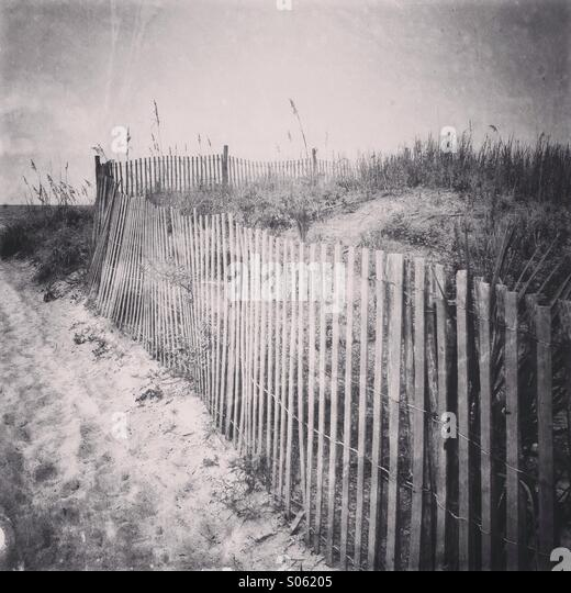 An old wooden beach fence runs along the sand dunes - Stock-Bilder
