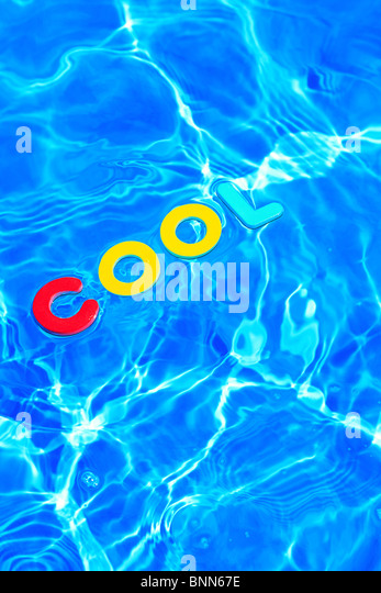 The word COOL made from foam letters floating on the water surface of a swimming pool - Stock-Bilder