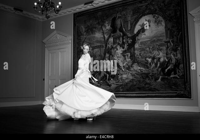 Wedding preparations, Bride dancing against old painting, Dorset, England - Stock Image