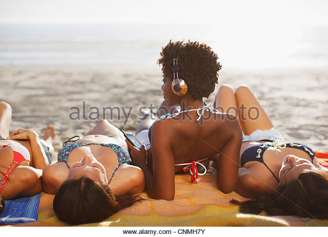 Women sunbathing together on beach - Stock Image