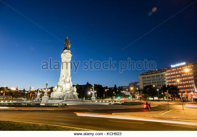 Lisbon Portugal Praca do Marques de Pombal roundabout traffic circle statue dusk car lights light streaks night - Stock Image