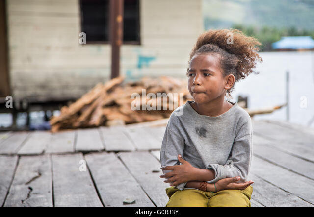 JAYAPURA, WEST PAPUA, INDONESIA - CIRCA FEBRUARY 2016: Papuan girl sitting with a dreamy face - Stock Image