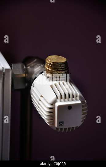 Coins on manual thermostat control on a central heating - Stock Image