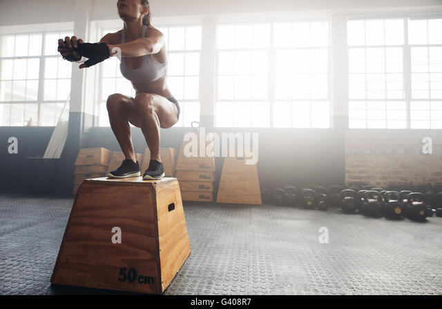 Shot of a young woman jumping onto a box as part of exercise routine. Fitness woman doing box jump workout at crossfit - Stock Image